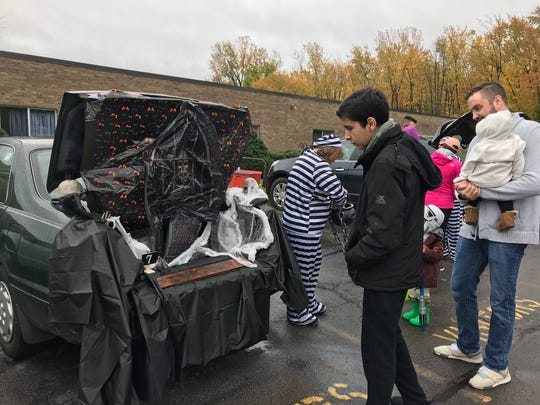 """Community members walk around the parking lot at the Sodus Rehabilitation and Nursing Center on Sunday for a """"trunk or treat"""" event. Kids dressed up and were able to trick or treat at different vehicles that had been filled with Halloween decorations."""