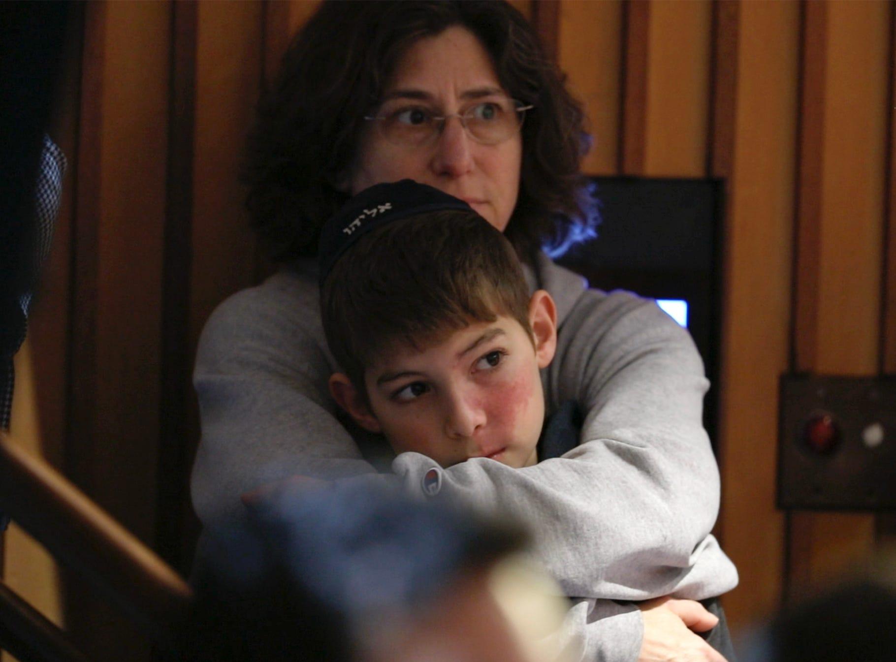 Francine Barnett holds her son, Elijah, as they listen to the speakers.