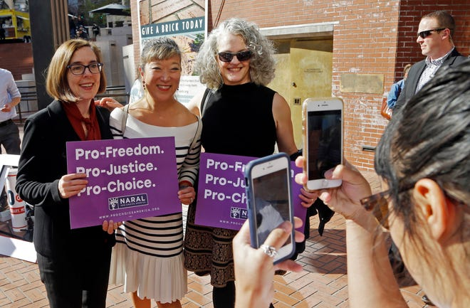 In this photo taken Oct. 17, 2018, Oregon Gov. Kate Brown, left, poses for photos with supporters after a rally in Portland, Ore. A measure to ban the use of state funds to pay for abortions is on the ballot in Oregon, the state with the least restrictive abortion laws in the nation. If it passes, Measure 106 would mean women who receive their health care through state Medicaid would not have insurance coverage for abortions.
