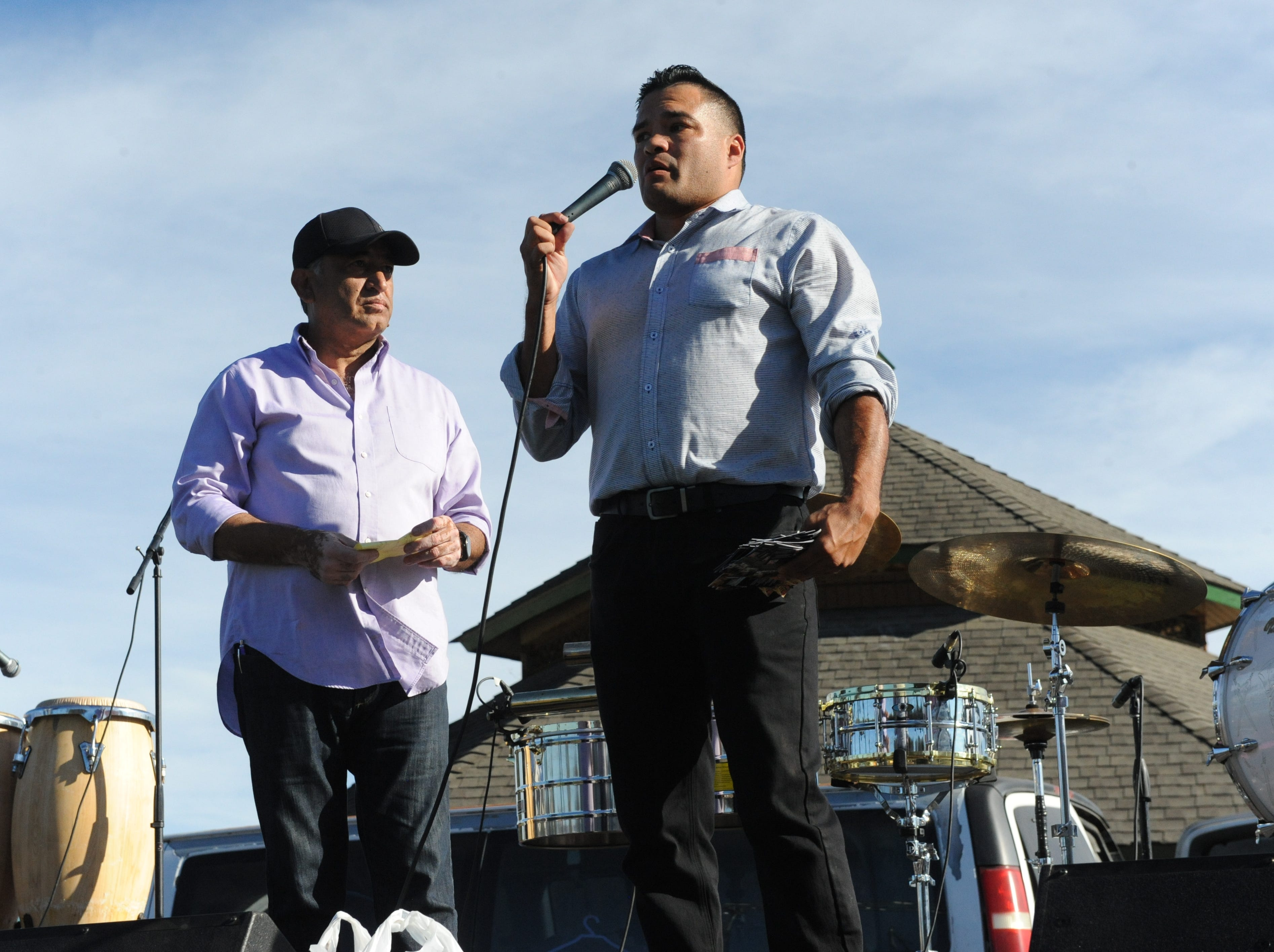 Victor Garcia, left, watches as former welterweight champion and Olympian, José Celaya, addresses the crowd Sunday at the Día de los Muertos celebration in Salinas.