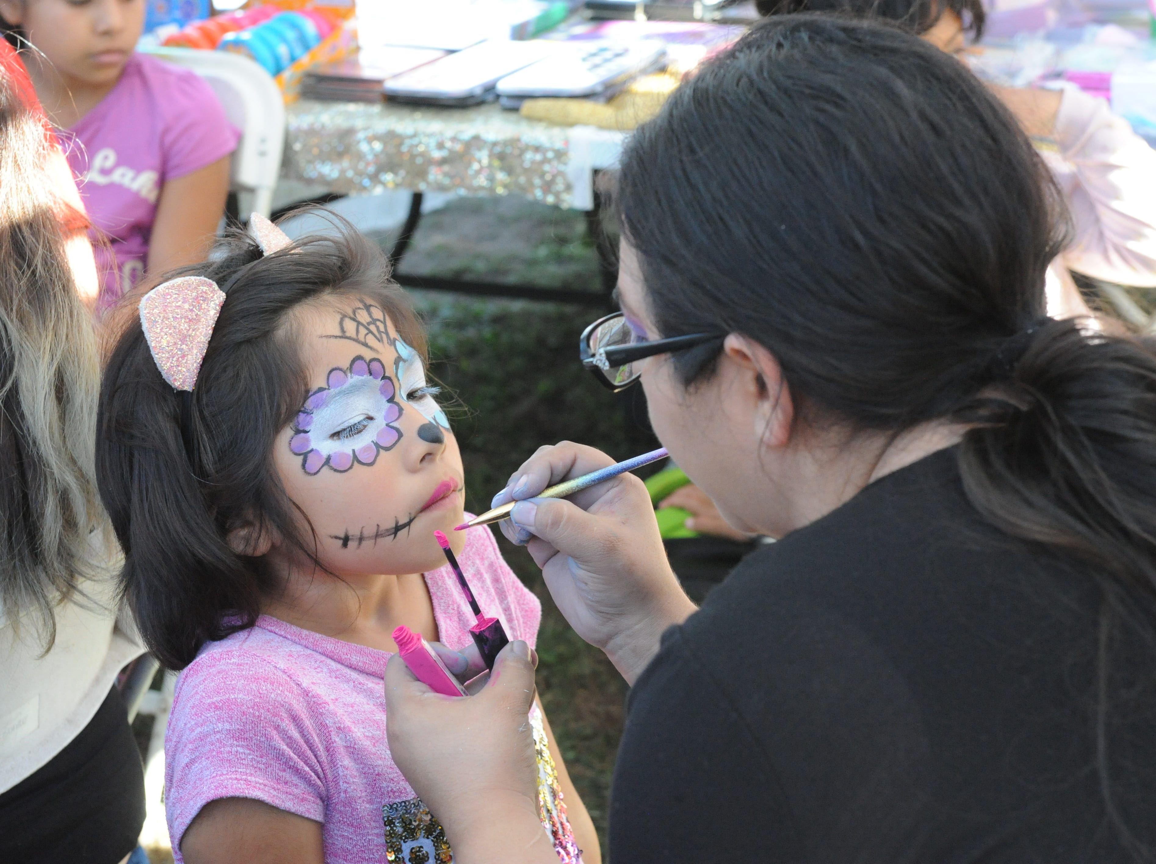 """A young girl gets her face painted in the image of La Calavera Catrina, or """"The Elegant Skeleton,"""" at Sunday's Día de los Muertos celebration in Salinas."""