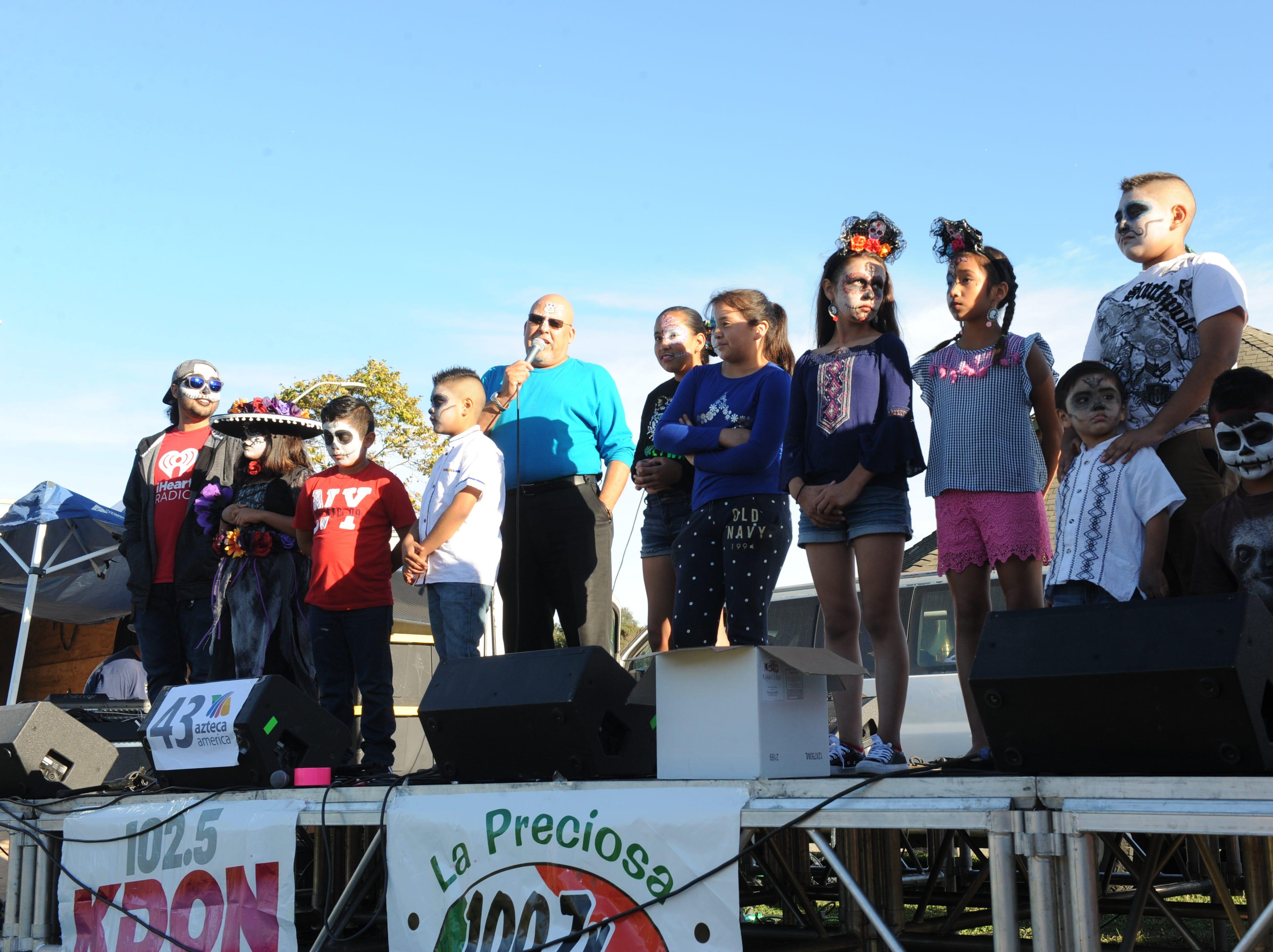 """Youth participate in the Día de los Muertos' La Calavera Catrina, or """"The Elegant Skeleton,"""" contest in Salinas on Sunday. Jose Valenzuela, of La Preciosa radio, announced the young contestants."""