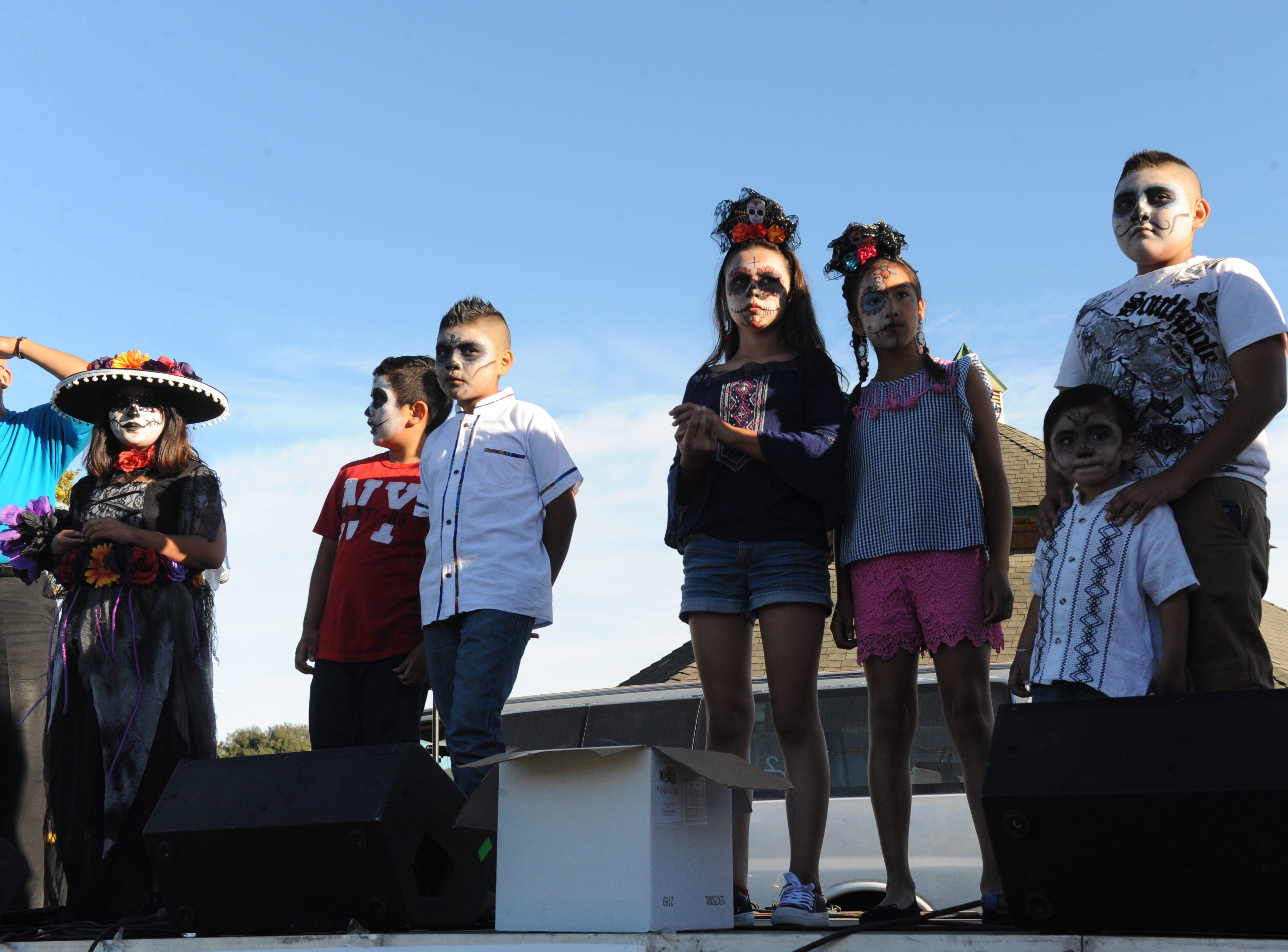 """La Calavera Catrina, or """"The Elegant Skeleton,"""" contestants gather on stage at Sunday's Día de los Muertos celebrations."""