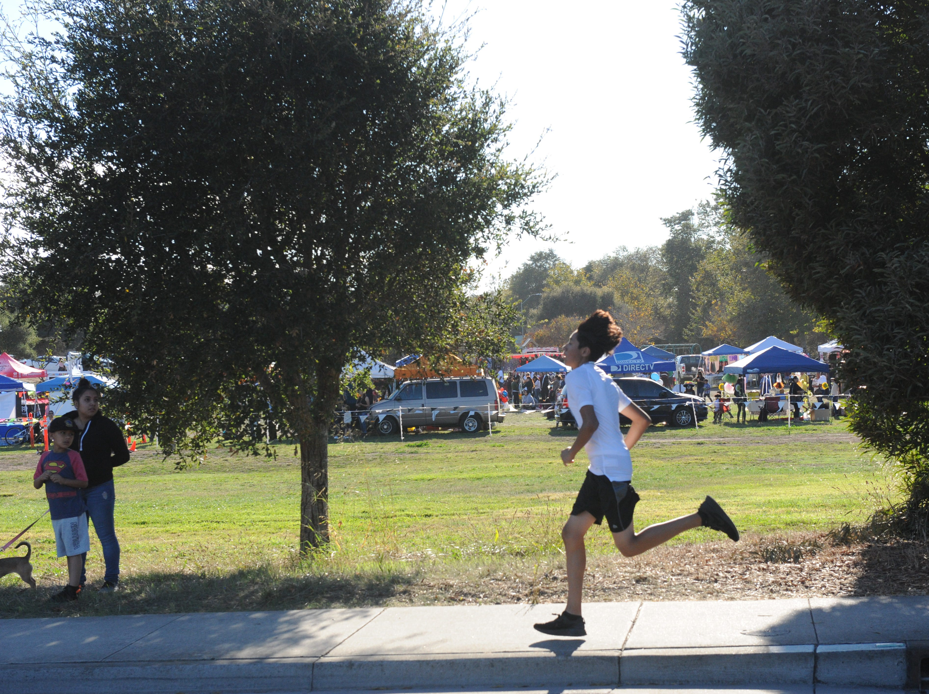 A runner races down Freedom Parkway at Sunday's Día de los Muertos 5k benefit run, with the festivities in the distance at Natividad Creek Park.