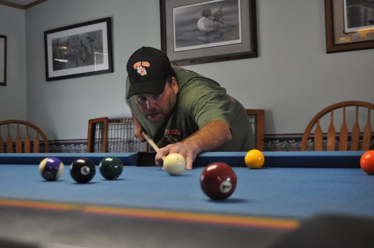 Kenny Watts plays pool at his home in Greenwood, Delaware. The Vibrio vulnificus affected the muscles in his entire arm, including his shoulder, which required months of occupational therapy to relearn simple tasks.