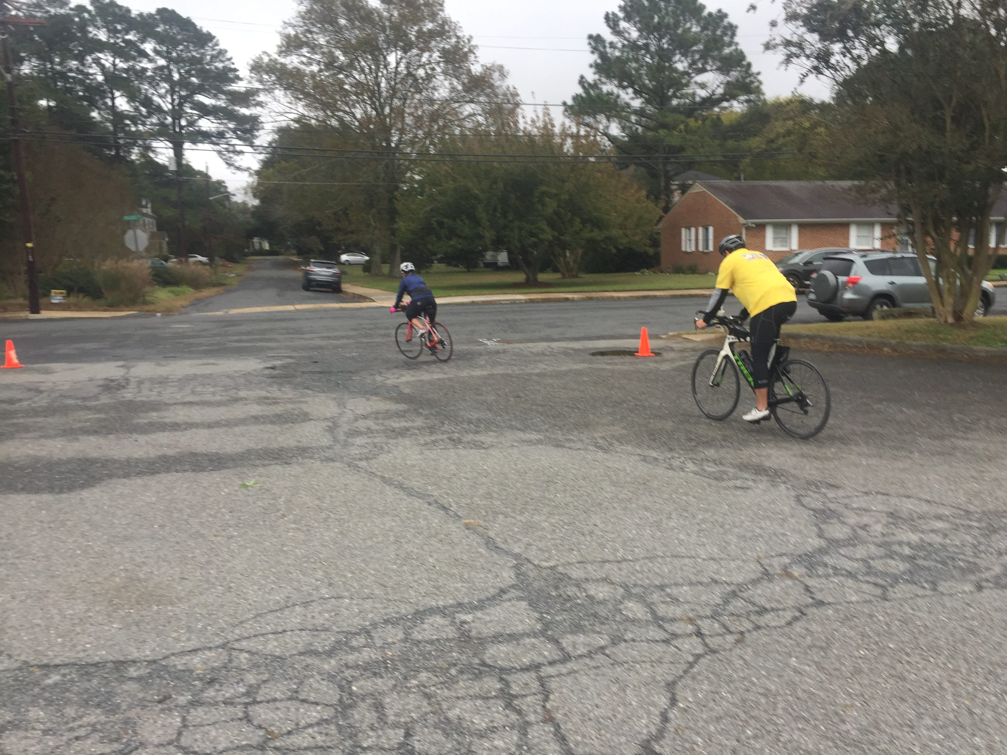 A pair of bicyclists head out of the parking lot at the Historic Onancock School during the Bike & Brew event on Saturday, Oct. 27, 2018. The event, held following the CBES Bike Ride, highlighted the Eastern Shore of Virginia's two breweries, Black Narrows Brewing Co. and Cape Charles Brewing Co.