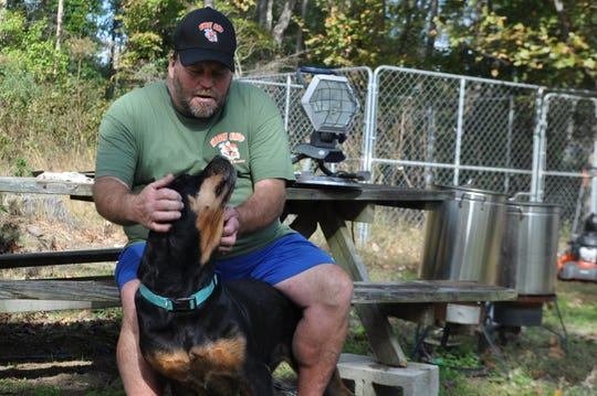 Kenny Watts, 53, sits with his rottweiler, Sam, in his backyard at his home in Greenwood, Delaware, on Oct. 24, 2018.