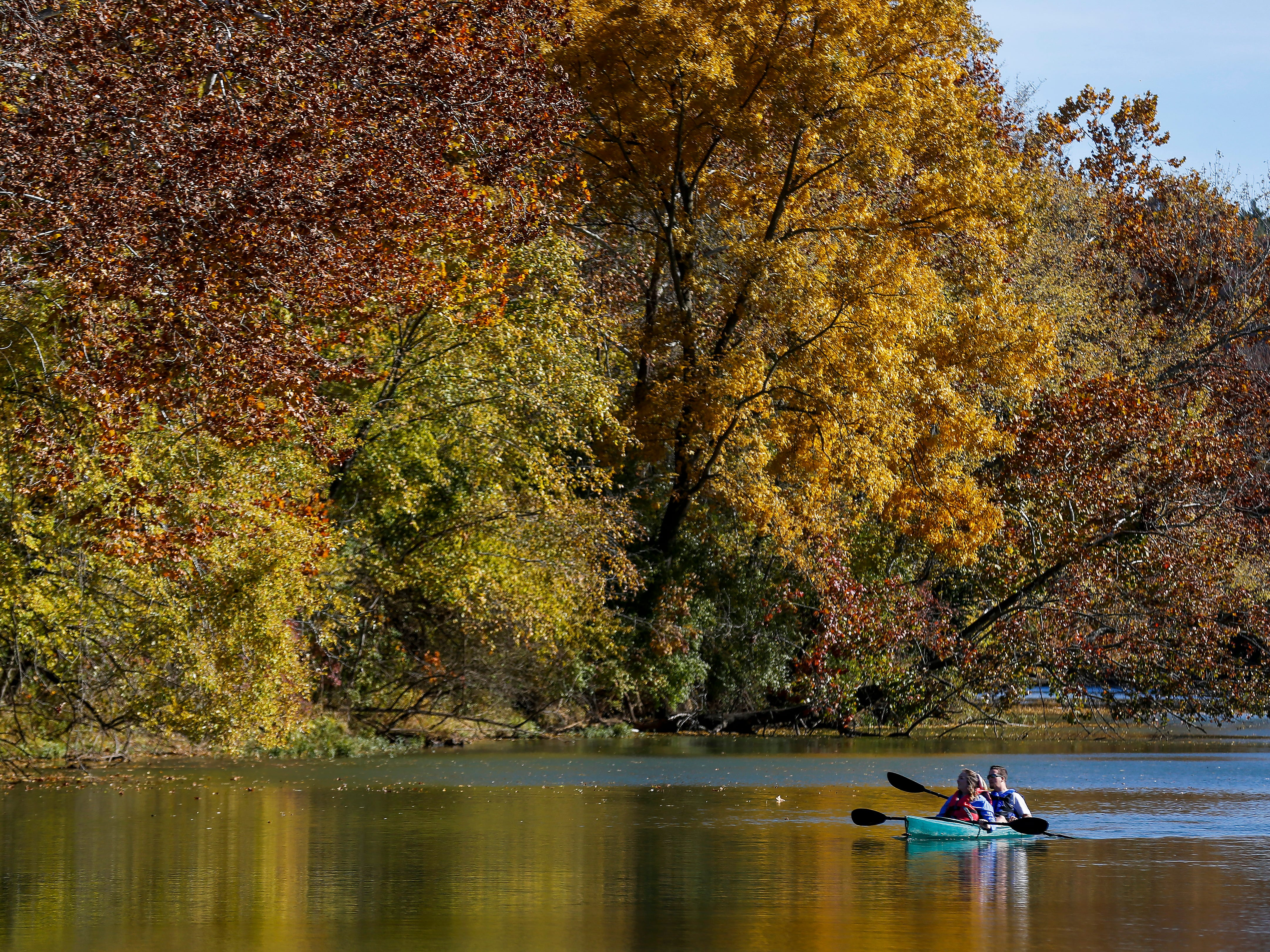 With some colorful fall trees as a backdrop, a couple paddles down the James River on Monday, Oct. 29, 2018.