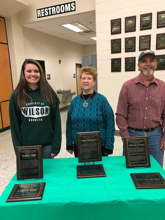 Hannah Rose, Pat Via and Kenny Snyder stand behind wall plaques in the Wilson Memorial gym lobby. The trio was inducted into the Wilson Memorial Hall of Fame class Friday night.