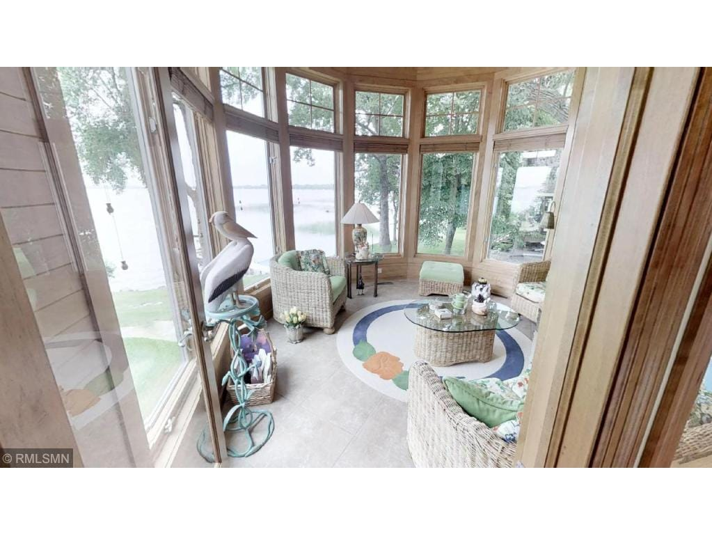 Directly off the back of the kitchen is a sun porch covered in arching windows.