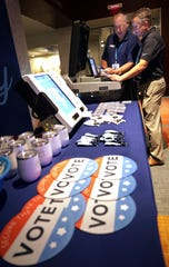 Election Systems & Software Vice Presidents of Sales Bryan Hoffman, right, and Mac Beeson look at some of the company's election equipment in the vendor display area at a National Association of Secretaries of State convention in Philadelphia on July 14, 2018. Experts say top election vendors have long skimped on security in favor of convenience and use proprietary systems, making it more difficult to detect election meddling.