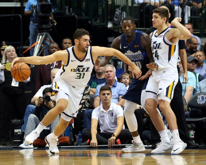 Utah Jazz forward Georges Niang (31) drives the ball past Dallas Mavericks forward Dorian Finney-Smith (10) and Jazz guard Grayson Allen (24) in the first half of an NBA basketball game Sunday, Oct. 28, 2018, in Dallas. (AP Photo/Richard W. Rodriguez)