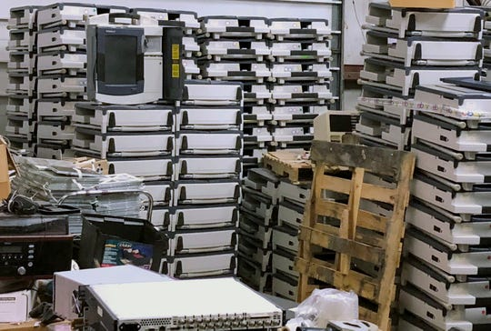 This July 18, 2018, photo shows a warehouse in North Canton, Ohio, where previously used AccuVote TSX voting machines purchased from an Ohio county are sold by an electronics recycler them for less than $100 apiece. The antiquated, vulnerable machines, still in use in across the nation, are a legacy of an industry that has long stressed convenience over the kind of security experts say is required to protect the nation's elections systems from sophisticated hackers.