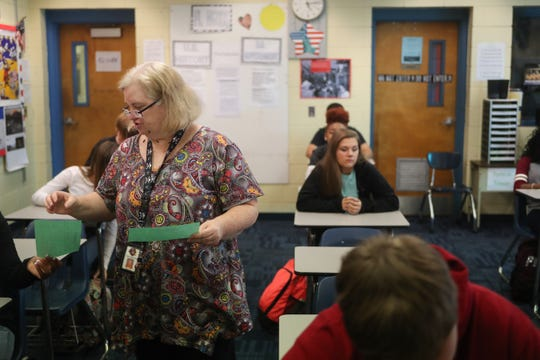 Sneads High School Teacher Beth Sloan collects Hurricane Michael information sheets in her homeroom class Monday, Oct. 29, 2018 as school resumes in Sneads, Fla. after Hurricane Michael hit the community three weeks ago.
