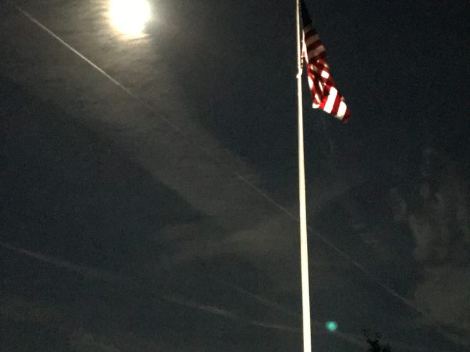 A full moon shines on the flag at the National Cemetery off Aplachee Parkway.