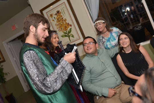 """John Whitty reads a clue to guests at the E.N.D. It! Mystery Dinner Theater fundraiser """"A Wedding Knight To Remember"""" on Oct. 20 at Santa Lucia River Club at Ballantrae."""