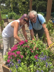 Dina DeGroat, left, and Norm Gagnon embrace a dementia friendly community by watering neighboring gardens.