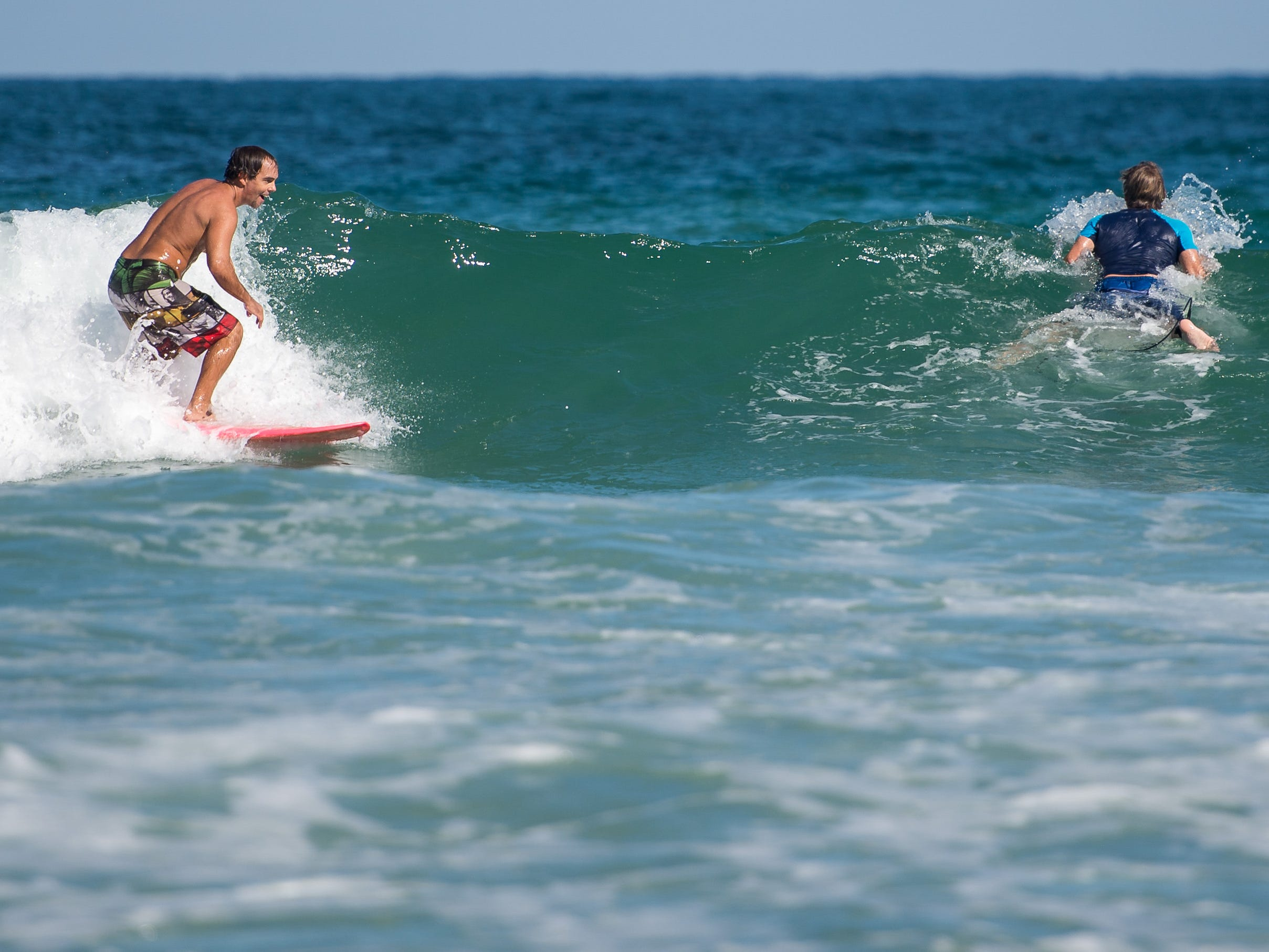 """Shane Hammond (left), of Fort Pierce, catches a wave and passes by fellow surfer Jim Spencer, of Port St. Lucie, on Monday, Oct. 29, 2018, at Fort Pierce Inlet State Park in St. Lucie County. Hammond said he came out to surf at the same spot last weekend for about an hour, and felt the effects from red tide almost immediately. """"I was actually down for the count all weekend, that was rough,"""" he said. Hammond, who usually appreciates the ocean for its restorative properties, added """"I've never seen, or felt or experienced anything like this…I hope we can fix this."""" Spencer, who Hammond called a """"die-hard surfer,"""" said he came out to surf a couple of days ago and couldn't even get in the water."""
