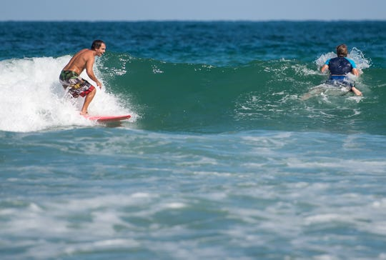 "Shane Hammond (left), of Fort Pierce, catches a wave and passes by fellow surfer Jim Spencer, of Port St. Lucie, on Monday, Oct. 29, 2018, at Fort Pierce Inlet State Park in St. Lucie County. Hammond said he came out to surf at the same spot last weekend for about an hour, and felt the effects from red tide almost immediately. ""I was actually down for the count all weekend, that was rough,"" he said. Hammond, who usually appreciates the ocean for its restorative properties, added ""I've never seen, or felt or experienced anything like this…I hope we can fix this."" Spencer, who Hammond called a ""die-hard surfer,"" said he came out to surf a couple of days ago and couldn't even get in the water."