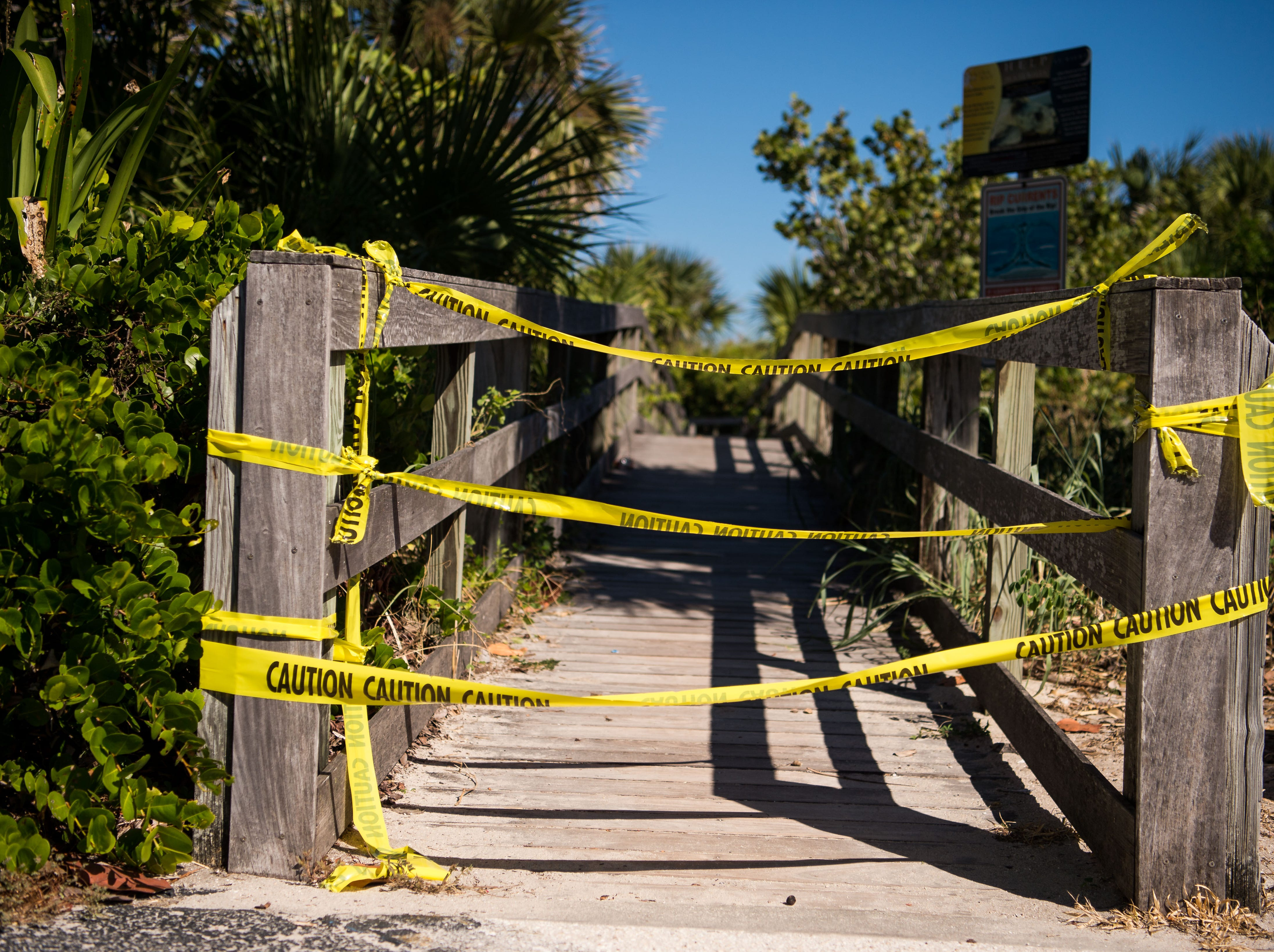 Caution tape closing off a walkway to the beach at Pepper Beach Park on North Hutchinson Island is seen Monday, Oct. 29, 2018, in St. Lucie County. Contractors said dead fish have been cleared from many of the beaches, and they should be able to re-open after inspection.