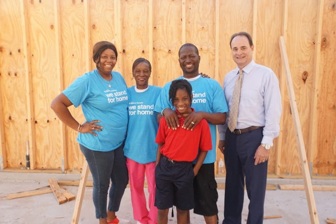 Indian River Habitat homebuyers Roseline Civil and Carla & Robert Jones and their granddaughter, Nalay, and The Moorings Yacht & Country Club CEO Craig Lopes.