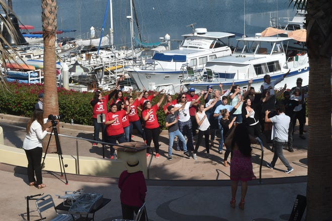 Business owners in Ventura and other community members record a music video at Ventura Harbor Village on Oct. 25. The video is aimed at lifting the local economy as businesses rebound from the Thomas Fire.