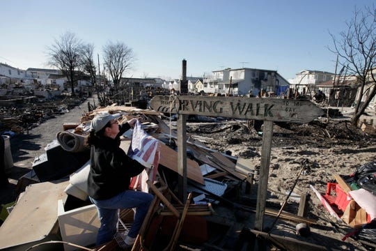 In this November 2012 photo, Louise McCarthy places an American flag on a street sign for Irving Walk in the Breezy Point neighborhood of Queens, N.Y. The sign survived a fire that swept through the seaside community during Superstorm Sandy two weeks earlier.