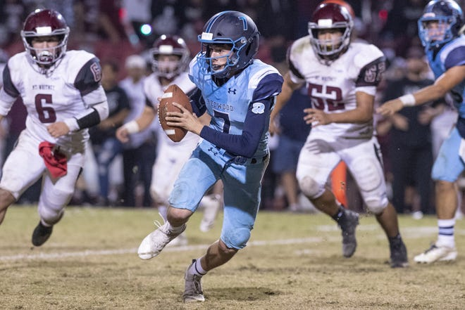 Redwood quarterback Julian Sanchez scrambles against Mt. Whitney in the annual Cowhide football game on Friday, October 26, 2018.