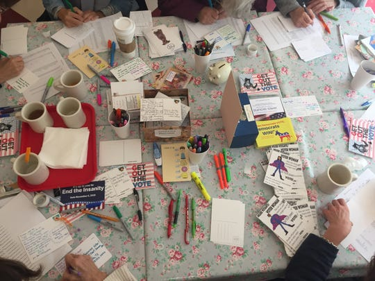 Volunteers with Indivisible Westchester work on colorful postcards ahead of the 2018 midterm elections at The Voracious Reader in Larchmont, Oct. 26, 2018.