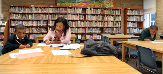 Chantel Laventure-Louis helps her sons, Jovanny Louis, left, and Reynaldo Louis Jr., right, with their homework at Pearl River Middle School Oct.17, 2018.