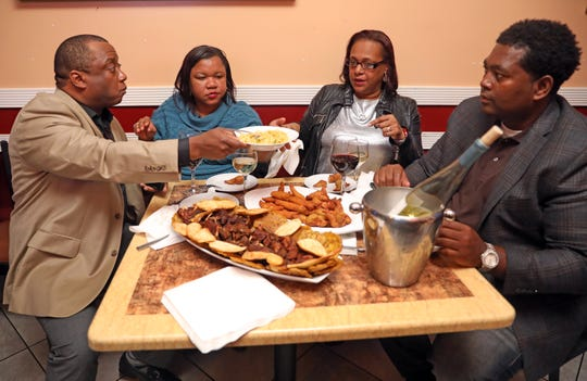From left, Louis Mathieu and his wife Carline Mathieu, Miriam Agenor, and Wilkinson Agenor, enjoy traditional Haitian food with friends, while listening to a live Haitian band called DJazz NewYork LA perform at La Baguette d'Or bistro in Spring Valley on Oct. 20, 2018.