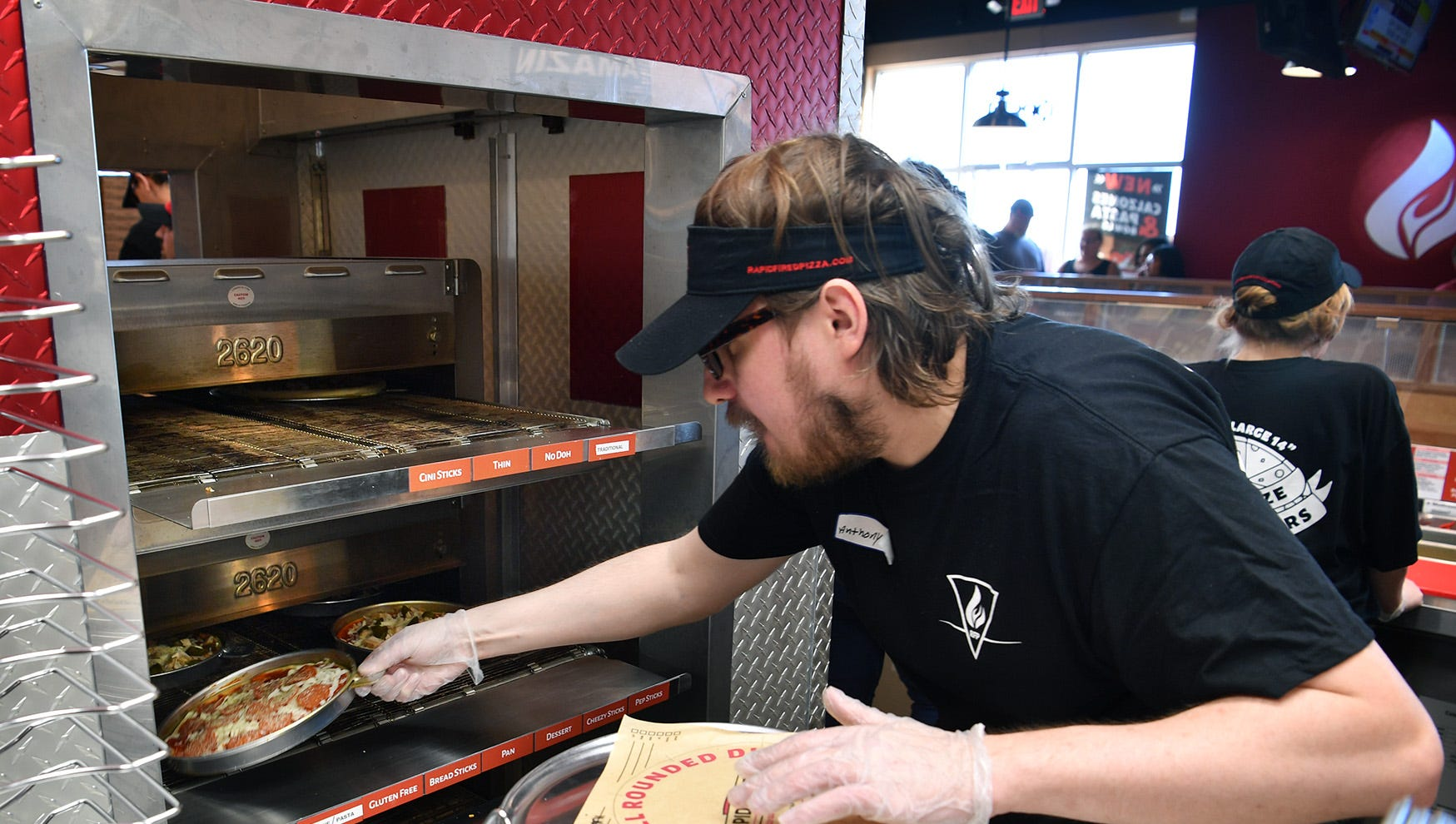 Anthony Sims places a freshly-made pizza into a special convection oven at Rapid Fired Pizza Monday morning. The new restaurant offered 500 free pizzas for their grand opening.