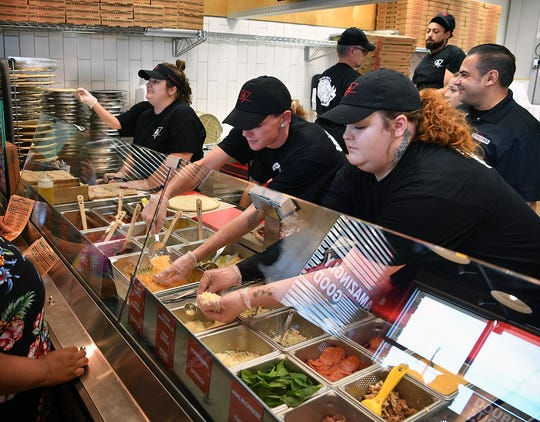 As a customer goes down the line, workers at Rapid Fired Pizza custom-make the pizza with fresh ingredients. The new eatery opened on Taft near Southwest Parkway Monday morning.
