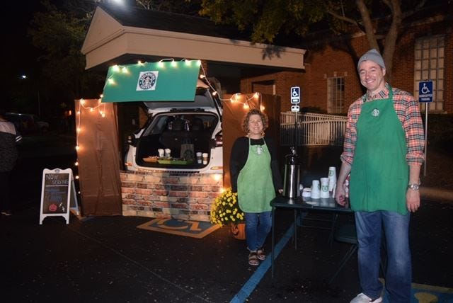 Newly installed senior minister Dr. Mark Bender, right, and his wife Jodi welcome trunk-or-treaters at First Christian Church's annual event Sunday. Young trick-or-treaters visited decorated car trunks and enjoyed festivities in the gym during the church's Halloween event.