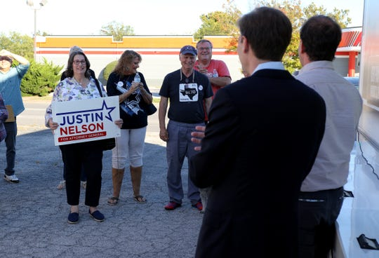 Supporters listen to Justin Nelson, Texas attorney general candidate, as he gives a speech Sunday, Oct. 28, 2018, outside the Wichita County Democratic office.