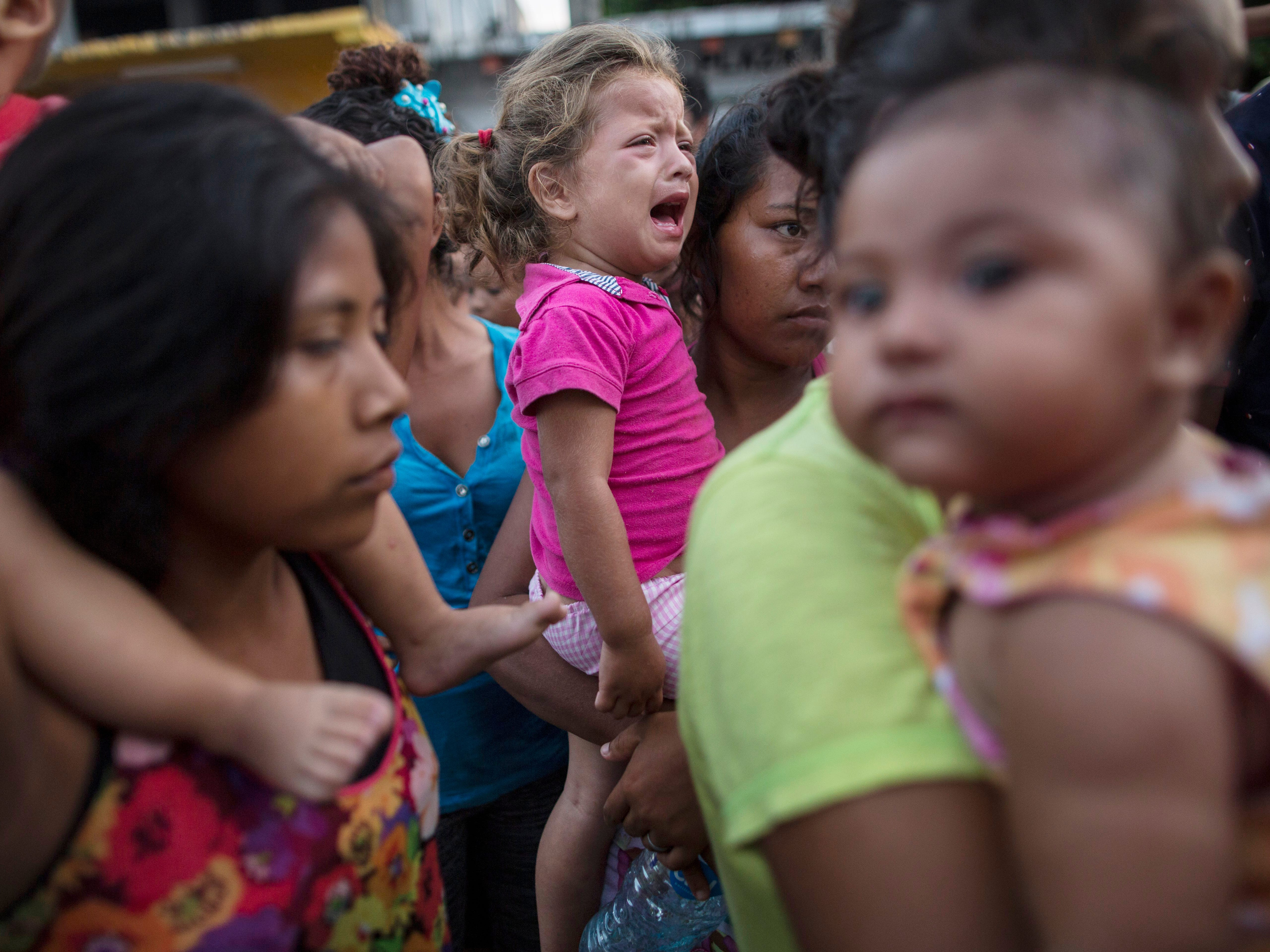 Delsy Alondra, 2, cries while waiting with her mother to receive donated food in Tapanatepec, Mexico on Oct. 28, 2018.