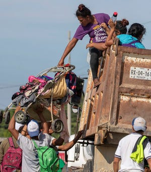 A woman lifts a baby carriage aboard a truck while she and others hitch a ride, Monday, in Tapanatepec, Oaxaca, Mexico. At least one migrant has died falling off a moving vehicle onto the pavement.