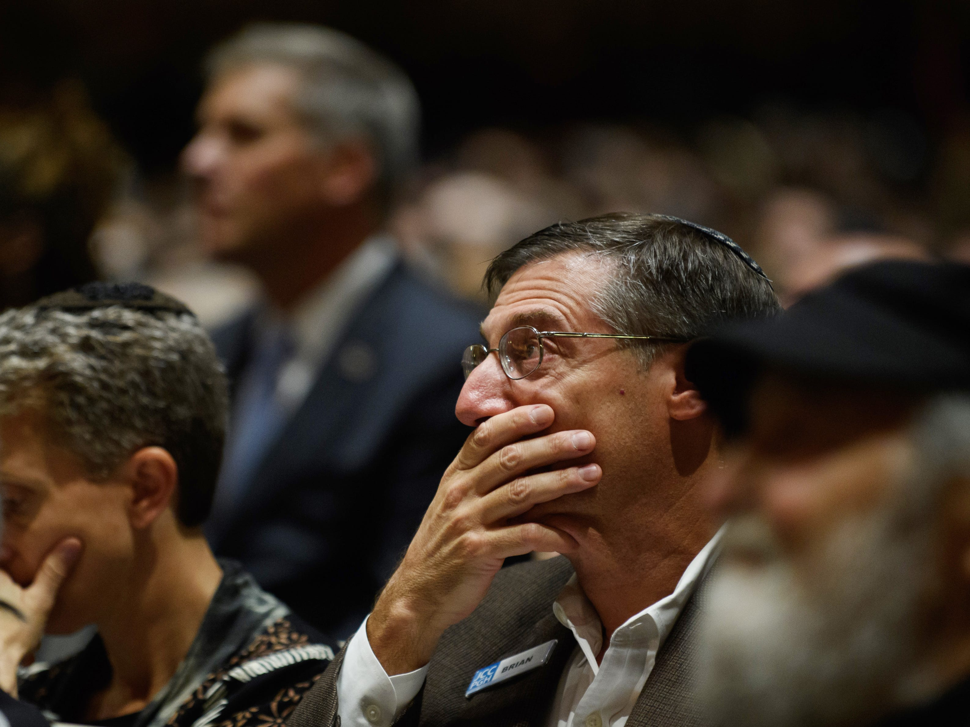 People listen to interfaith speakers on Oct. 28, 2018, at the Soldiers & Sailors Memorial Hall before a service to honor and mourn the victims of the mass shooting at the Tree of Life Congregation synagogue in Pittsburgh.