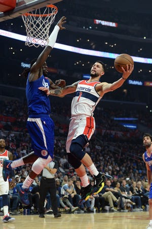 Wizards guard Austin Rivers (1) goes to the basket while defended by Clippers forward Montrezl Harrell during the second quarter at Staples Center.