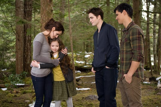 "Mackenzie Foy's first foray into the spotlight was in the ""Twilight"" franchise as the half-vampire, half-human daughter of Bella (Kristen Stewart) and Edward (Robert Pattinson, second from right, with Taylor Lautner)."