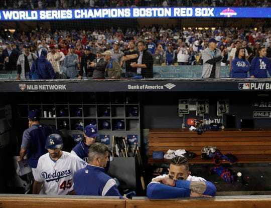 Manny Machado watches from the dugout as the Red Sox celebrate winning the decisive Game 5 of the World Series.