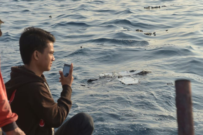 An Indonesian boatman takes pictures as debris from the ill-fated Lion Air flight JT 610 floats at sea in the waters north of Karawang, West Java province, on October 29, 2018.