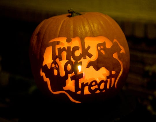 """A pumpkin carving in the shape of ghosts and the words """"Trick or Treat"""""""