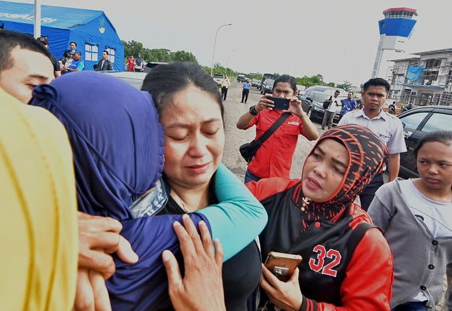 Putri is consoled for the loss of her husband and child who were passengers on board the ill-fated Lion Air flight JT 610, in Pangkal Pinang airport in Bangka Belitung province on October 29, 2018. A brand new Indonesian Lion Air plane carrying 189 passengers and crew crashed into the sea on October 29, officials said, moments after it had asked to be allowed to return to Jakarta.