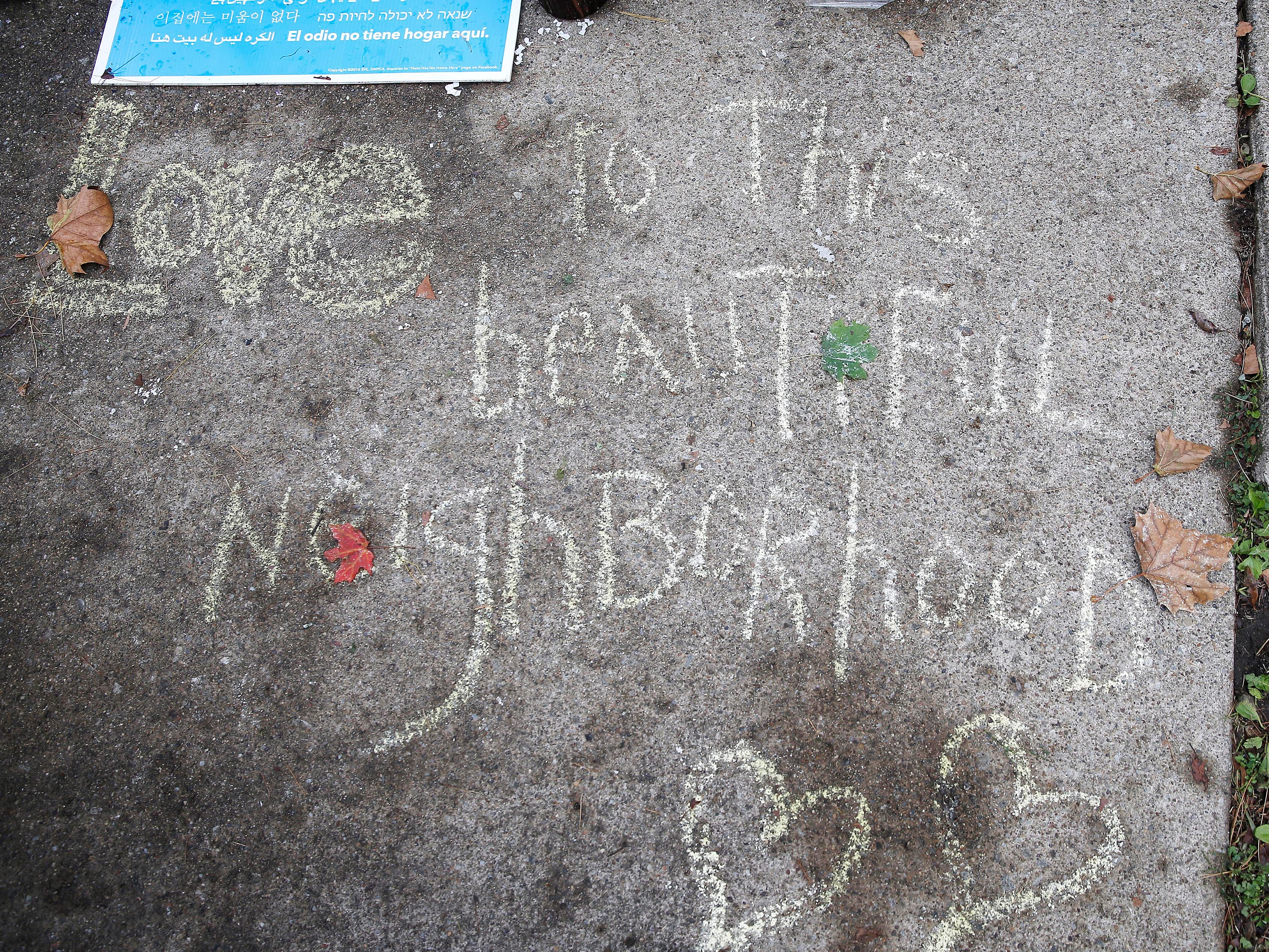 """Love this beautiful neighborhood"" is written on the sidewalk near the Tree of Life Congregation Synagogue in the Squirrel Hill neighborhood of Pittsburgh, Monday, Oct. 29, 2018."