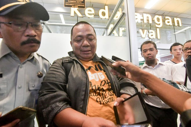 Sony Setiawan, center, speaks to journalists at Pangkal Pinang airport in Bangka Belitung, Indonesia, on Oct. 29, 2018, after missing his connecting flight, which crashed off the coast of Jakarta.