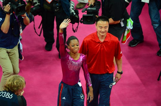 In a file photo from the 2012 Olympics, Gabby Douglas, left, celebrates with coach Liang Chow after her performance in the floor exercise in the women's individual all around final.