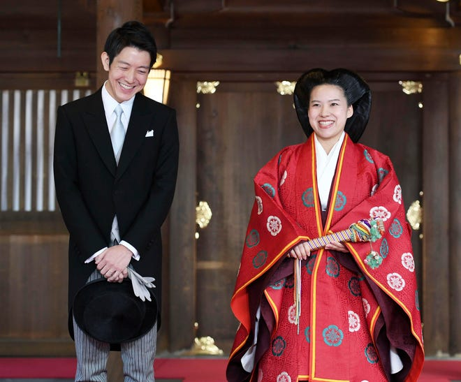 Japanese Princess Ayako, right, dressed in traditional ceremonial robe, and groom Kei Moriya, left, speak to the reporters after their wedding ceremony at Meiji Shrine in Tokyo, Monday, Oct. 29, 2018.