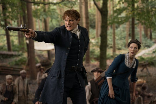 Jamie (Sam Heughan) and Claire (Caitriona Balfe) fend off Native Americans in a scene from 'Outlander.'