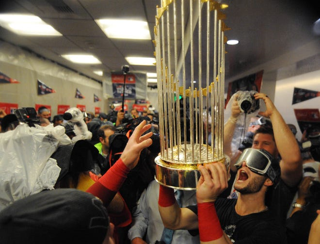 Red Sox players celebrate in the clubhouse after winning the World Series.